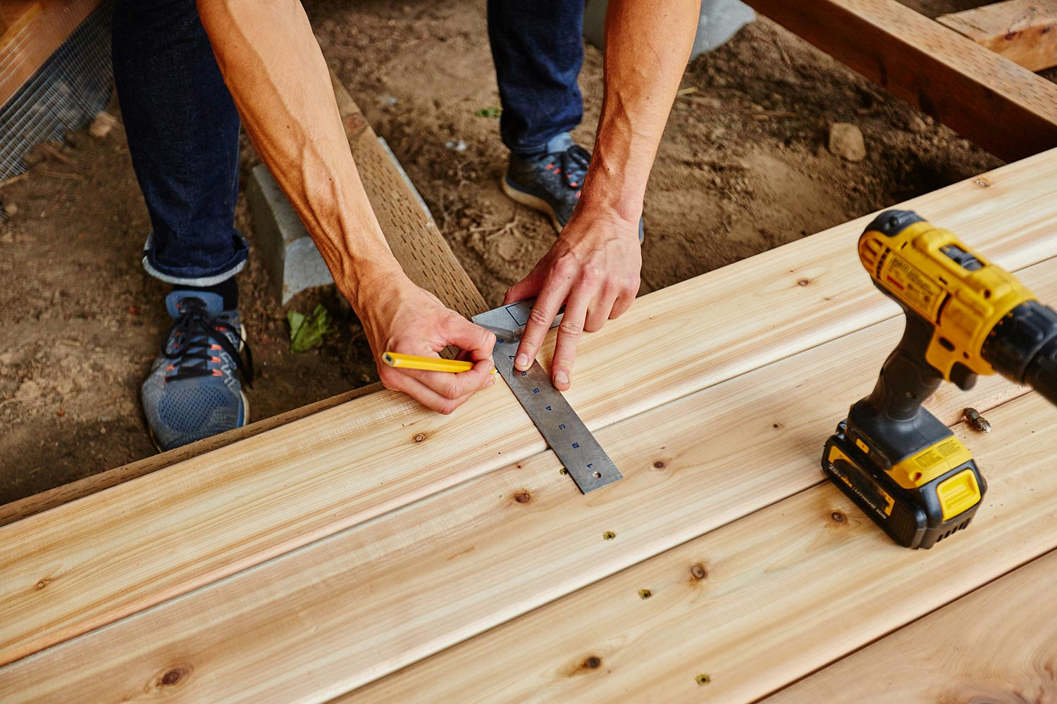Man measuring before drilling while building a deck during the spring